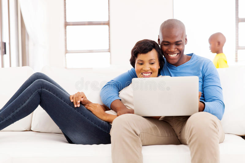 Afro american couple laptop. Happy afro american couple using laptop at home with their son on background stock image