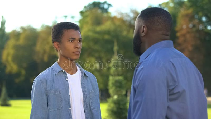Afro-american dad scolding teenage son outdoors, family conflict, communication stock photo