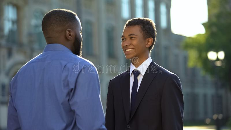 Afro-american father greeting son in suit outdoors university, prom celebration stock image