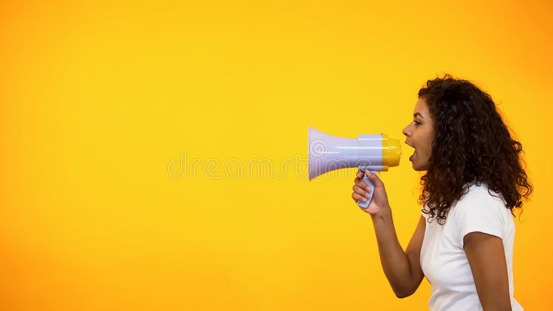 Afro-American girl screaming in megaphone, spreading information, awareness. Stock photo stock photography