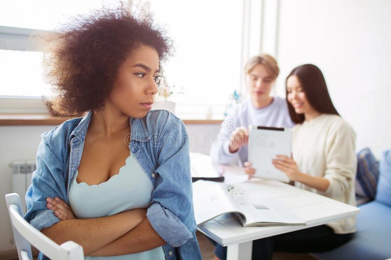 Afro american girl is sitting in front of camera and looking aside. She is angry and not happy at all. She jelaous. Her stock photos