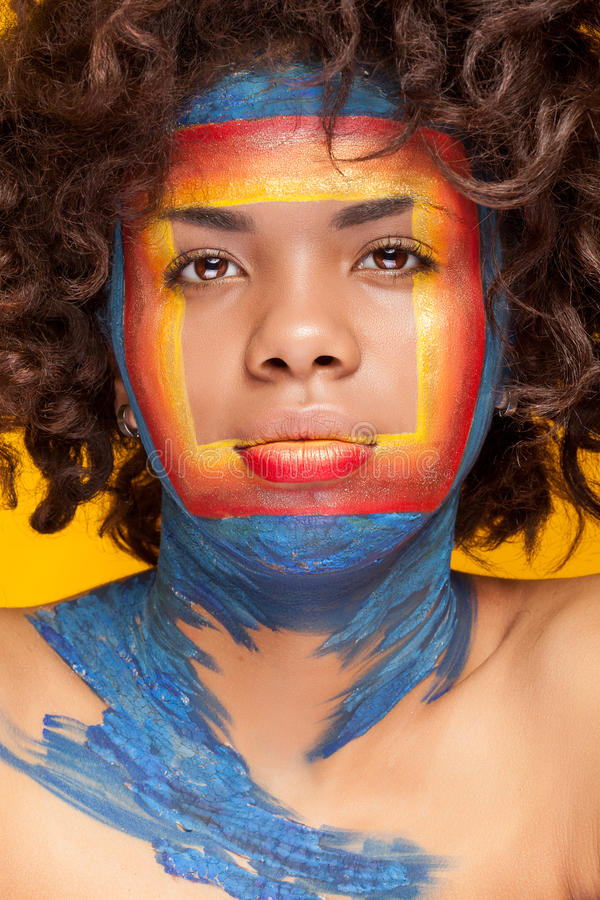 Afro american girl with a square beauty make up on her face. Studio photo on yellow background stock photos
