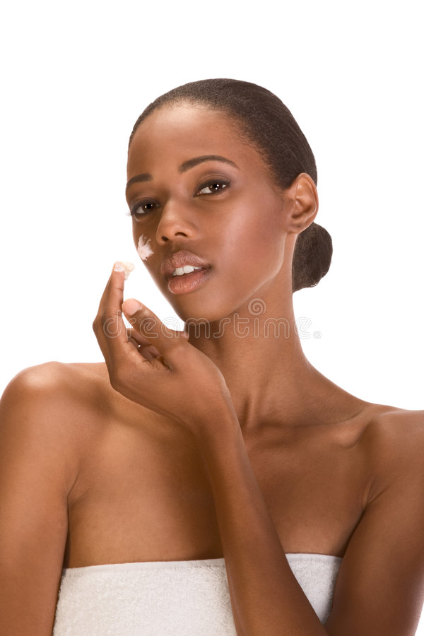Afro-American girl wrapped in towel cream on face stock images