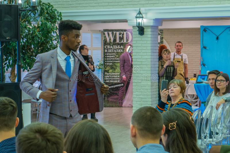 An afro-american groom model in a wedding suit wide opened. At the exhibition Wedding hassle 2019 took place in Kirov, Russia stock photos