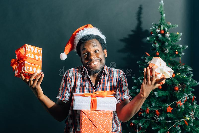 Afro american guy with charming smile holding Christmas gift in hands royalty free stock images