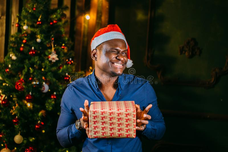 Afro american guy with charming smile holding Christmas gift in hands royalty free stock photos