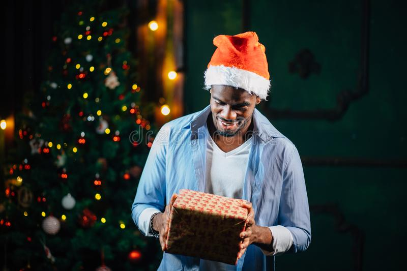 Afro american guy with charming smile holding Christmas gift in hands royalty free stock image