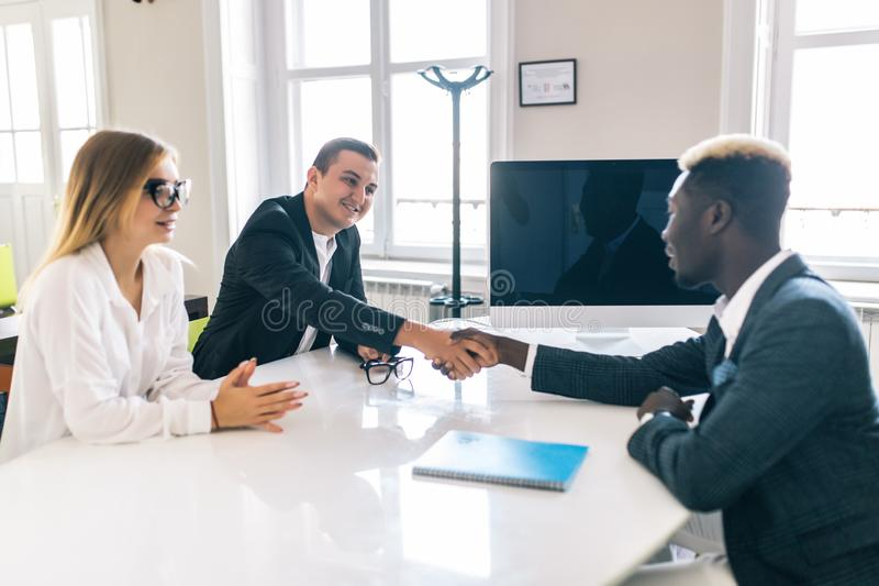Afro american investment advisor shaking hands with smiling man while consulting with young couple about financial savings stock image