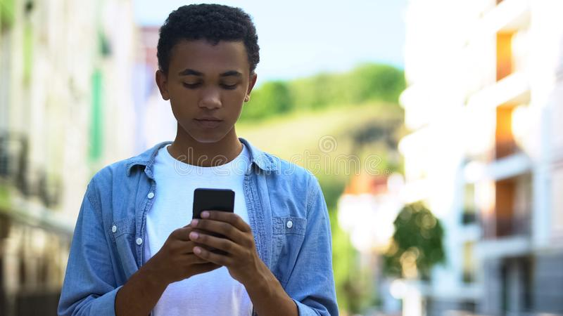 Afro-American male teenager chatting smartphone outdoors, online communication. Stock photo royalty free stock images