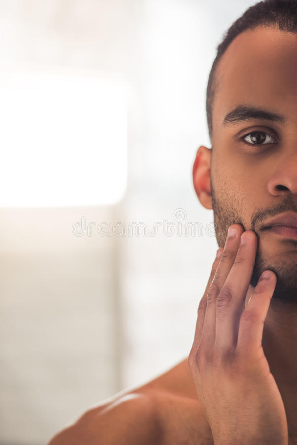Afro American man in bathroom. Cropped image of handsome Afro American man touching his face stock photos