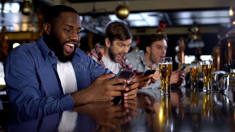 Afro-american man celebrating successful bet on match, online bookmaker on phone. Afro-american men celebrating successful bet on match, online bookmaker on royalty free stock photo