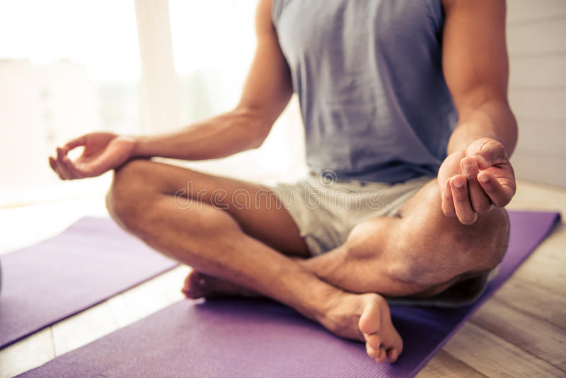 Afro American man doing yoga. Cropped image of handsome Afro American man in sports clothes meditating in lotus position on mat while doing yoga at home royalty free stock image
