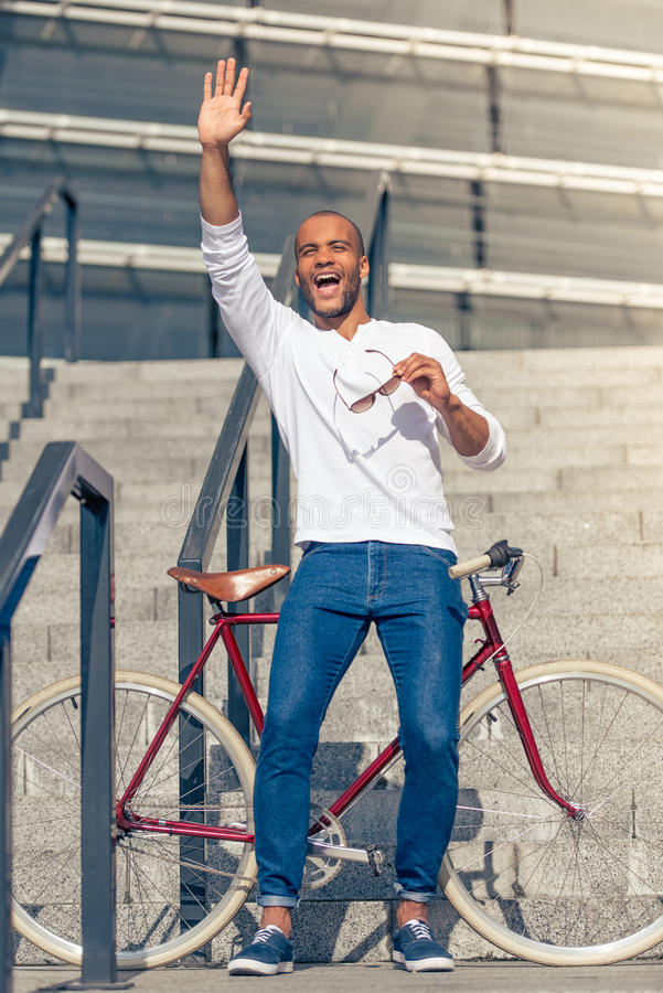 Afro American man. Full length portrait of handsome young Afro American man in casual wear waving and smiling, leaning on bike while standing on stairs outdoors royalty free stock photos