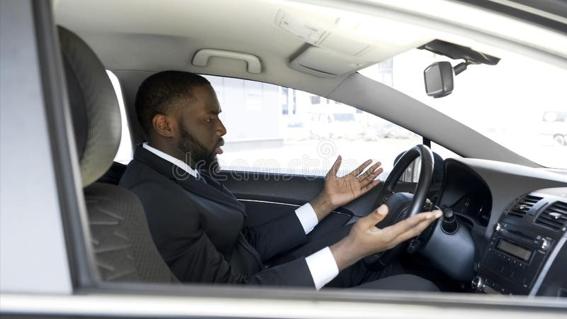 Afro-American man getting angry and nervous because of car breakdown, stress. Stock photo stock photo