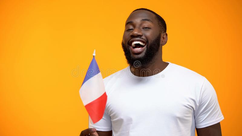 Afro-American man holding French flag on national holiday celebration, close-up royalty free stock photo