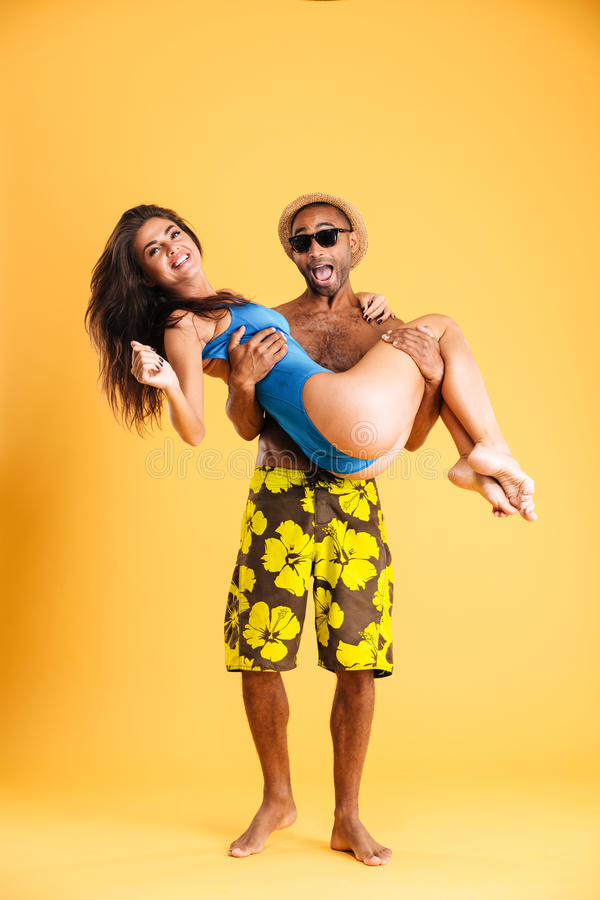 Afro american man holding his girlfriend with two hands. Afro american men holding his girlfriend with two hands isolated on orange background royalty free stock image