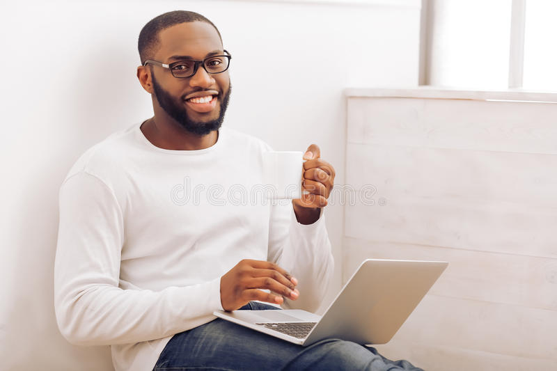 Afro American man at home. Handsome Afro American man in glasses is using a laptop, holding a cup and smiling while working at home royalty free stock photo