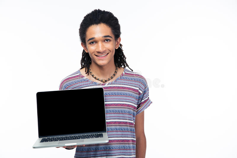 Afro american man showing blank laptop screen. Portrait of a smiling afro american man showing blank laptop screen isolated on a white background royalty free stock photography