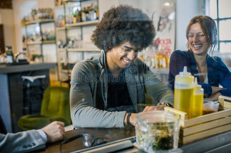 Afro american Man and woman smiling and talking while waiting lunch at bar.Multiethnic people having break time in royalty free stock image