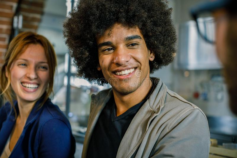 Afro american Man and woman smiling to friend or colleagues at bar.Multiethnic people having break time in restaurant stock photo