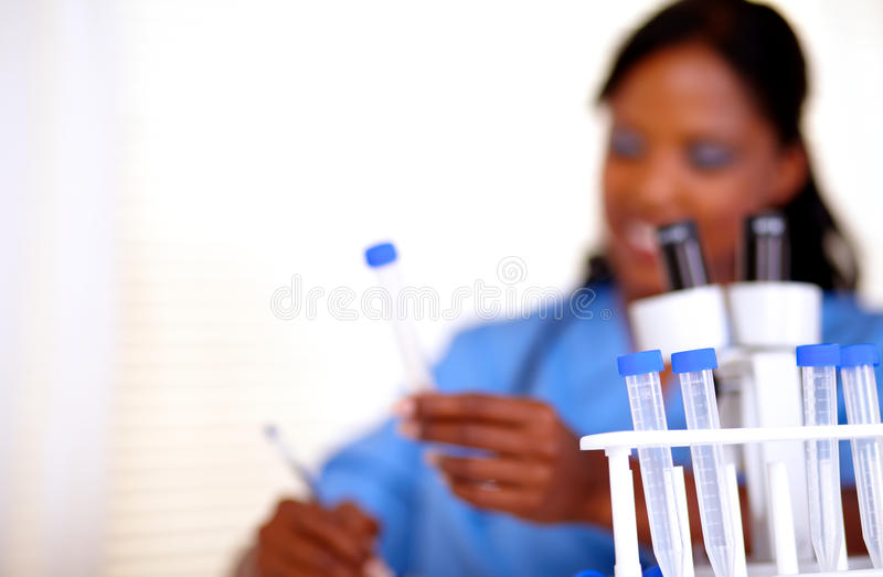 Afro-american nurse working with test tube stock photography