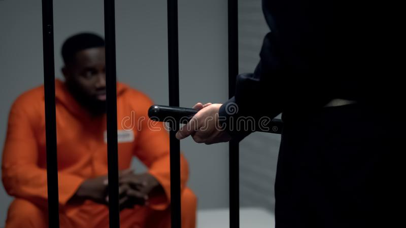 Afro-american prisoner in cell looking at jail guard with baton, harassment. Stock photo royalty free stock images