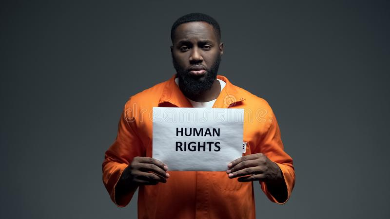 Afro-american prisoner holding human rights sign, ill treatment, awareness. Stock photo royalty free stock images