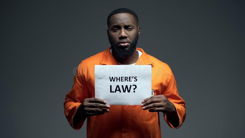 Afro-american prisoner holding where is law sign in cell, wrongly accused person royalty free stock image