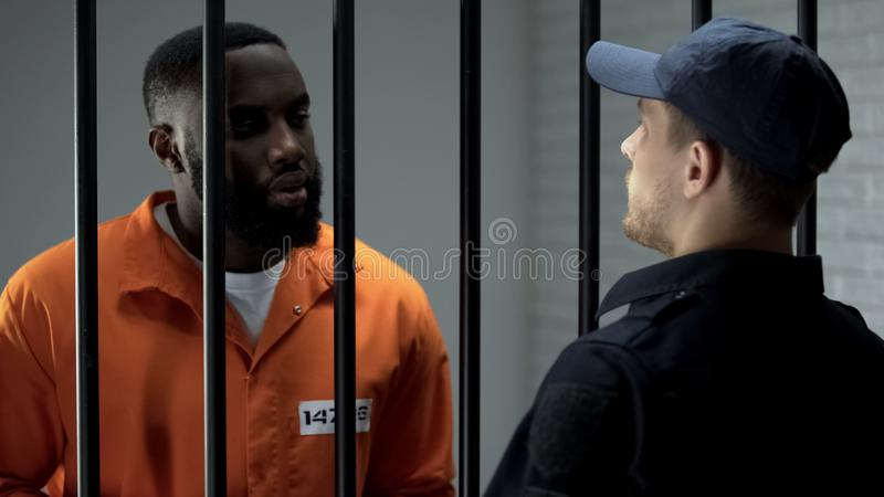Afro-american prisoner making arrangement with prison guard, corruption in jail. Stock photo stock photography