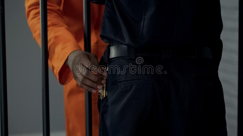 Afro-american prisoner stealing keys from security guard, preparing escape royalty free stock images