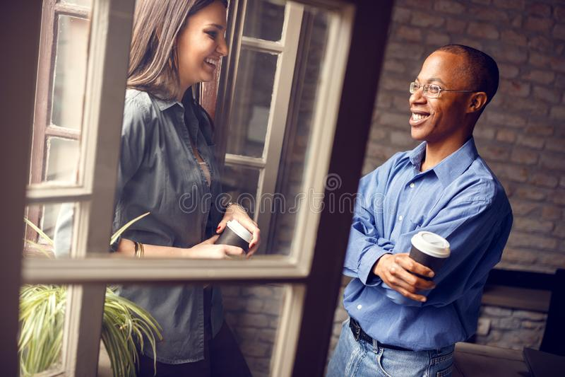 Afro-American supervisor talking with young woman stock image