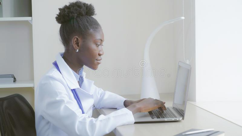 Afro american therapist typing on laptop stock photo