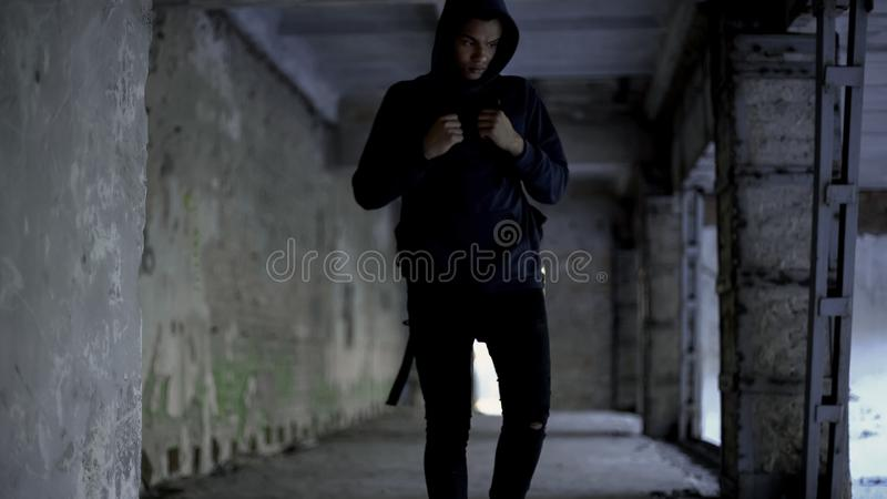 Afro-american walking in abandoned building, has no friends, racism problem. Stock photo stock photos