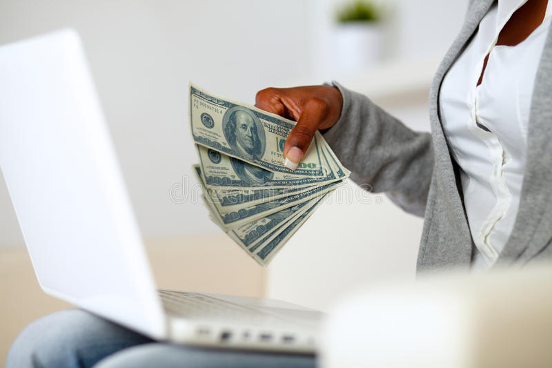 Afro-american woman holding plenty of cash money royalty free stock photography