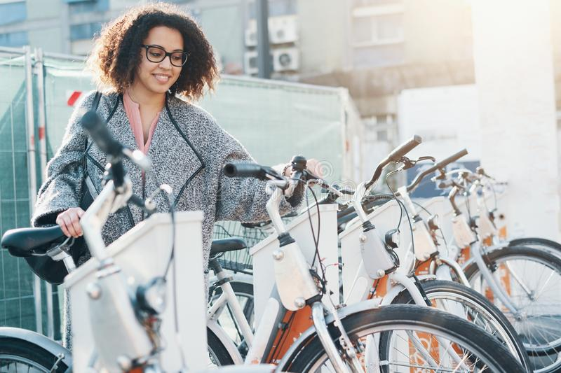 Afro american woman taking a bicycle in a bike sharing platform. Afro american woman taking a bicycle in a bike rental platform stock image