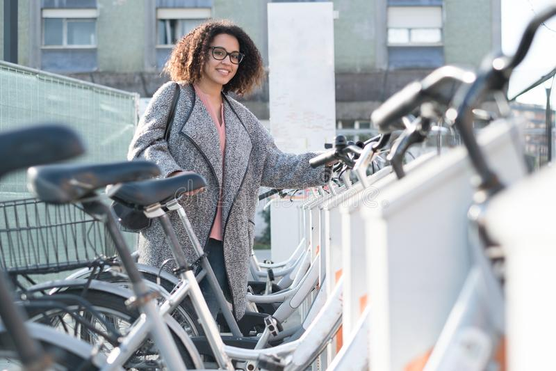 Afro american woman taking a bicycle. In a public rental station royalty free stock image