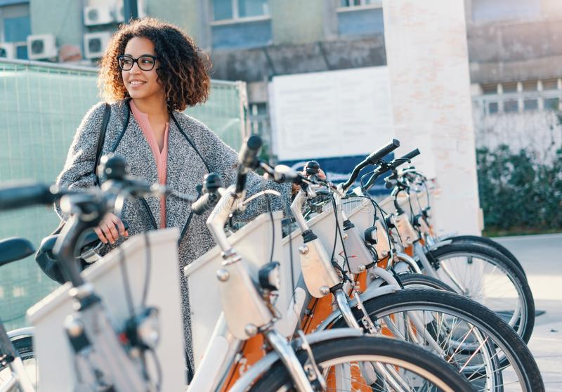 Afro american woman taking a bicycle. In a public rental station royalty free stock photos