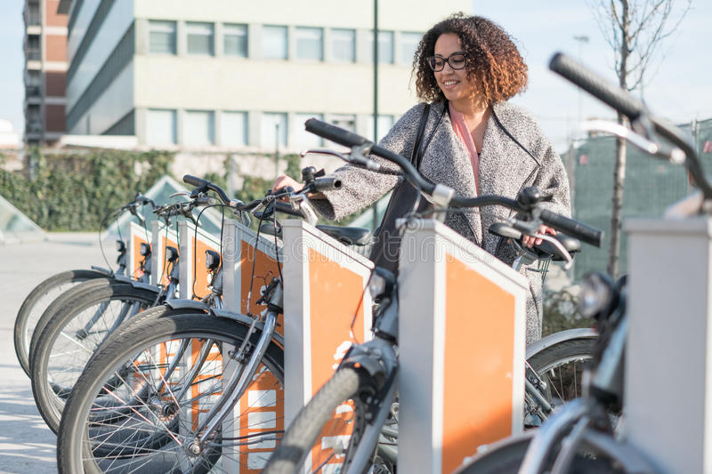 Afro american woman taking a bicycle. In a public rental station royalty free stock images