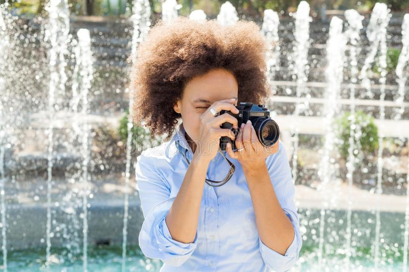 Afro American Woman Taking Photo With Retro Camera. Afro american woman with retro camera, female photographer taking photo with vintage camera at summer day stock image
