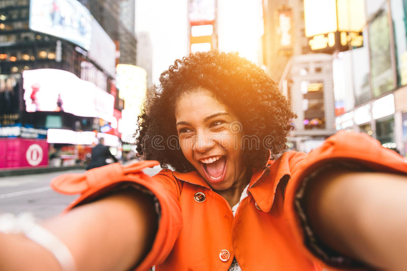 Afro american woman taking selfie in Time square, New york. Crazy portrait in the famous american square royalty free stock image