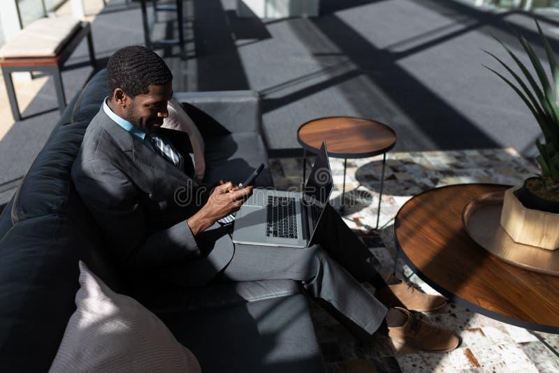 Afro-americano do homem de negócios com portátil usando o telefone celular no sofá no escritório fotografia de stock royalty free
