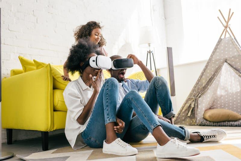 afro-americano nos auriculares da realidade virtual que têm o divertimento junto imagens de stock royalty free