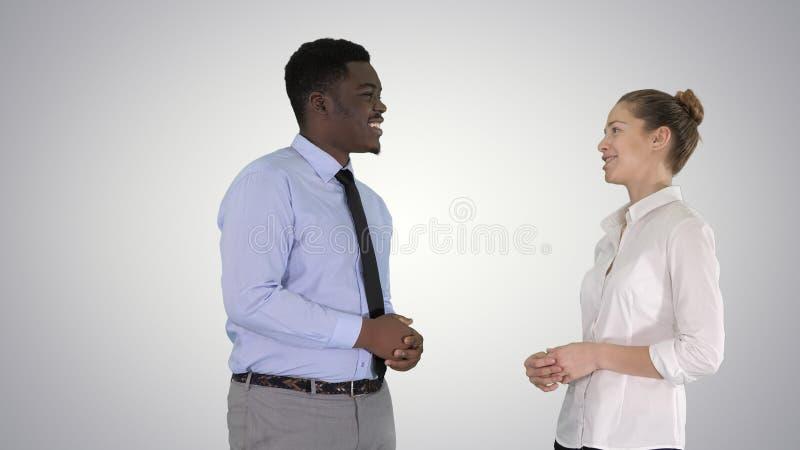 Afro Amerikaans kerel en meisje die over zaken op gradi?ntachtergrond spreken stock fotografie