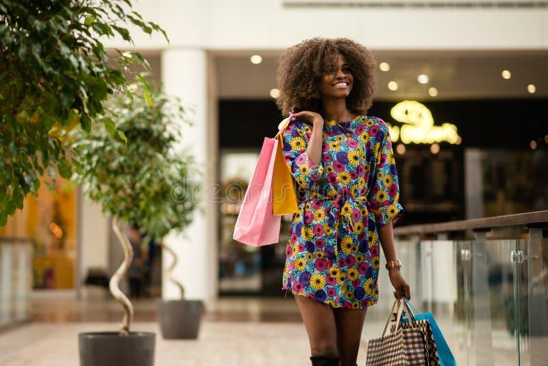 Afro-Amerikaans meisje die en met een partij op het winkelen zakken lopen glimlachen stock foto's