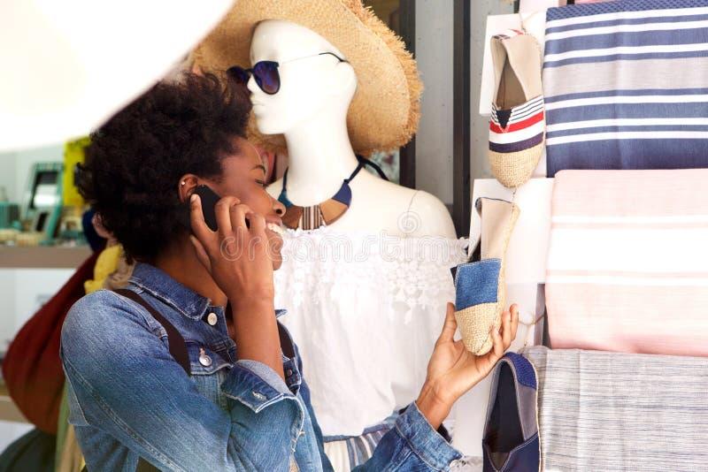 Afro Amerikaans meisje die voor schoenen in de stad winkelen en op slimme telefoon spreken stock foto's