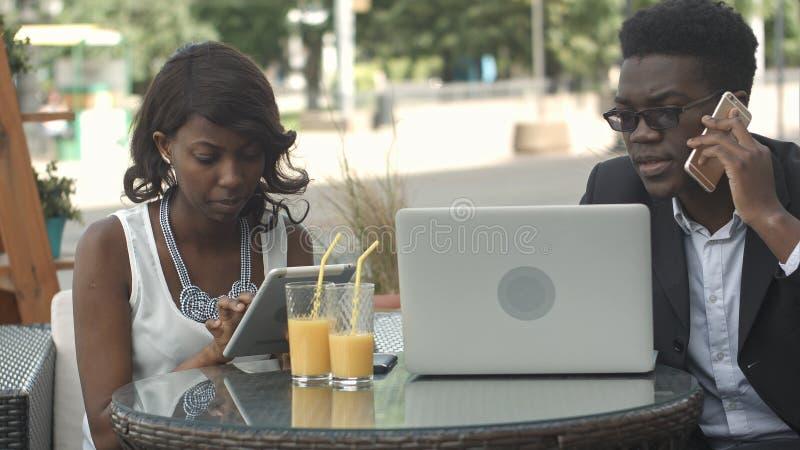 Afro-Amerikaanse bedrijfsman en vrouw die in moderne koffie samenwerken, die telefoongesprekken hebben, die laptop met behulp van stock afbeeldingen
