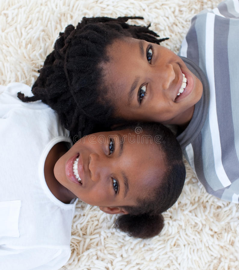 Afro-Amerikaanse broer en zuster op vloer stock afbeelding