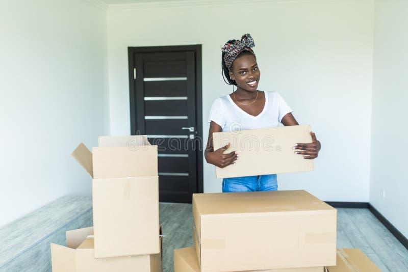 Afro Amerikaanse jonge Vrouw die een stapel van de voorbereiding van kartonkartons voor zich het bewegen dragen stock fotografie