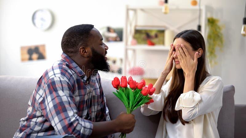 Afro-Amerikaanse mens die bos van tulpen voorstellen aan Kaukasisch meisje, verjaardagsgift stock afbeelding