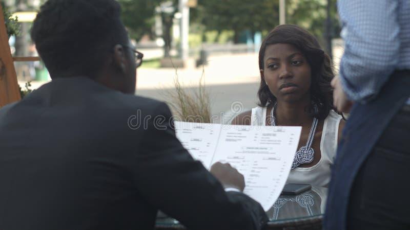 Afro Amerikaanse mens die in buitenkoffie opdracht geven tot, terwijl het zitten met zijn vrouwelijke partner stock afbeelding